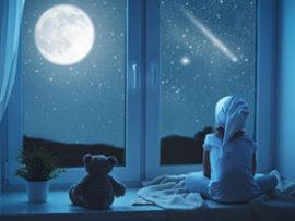 Schlaflieder: Kind mit Teddy schaut zum Mond
